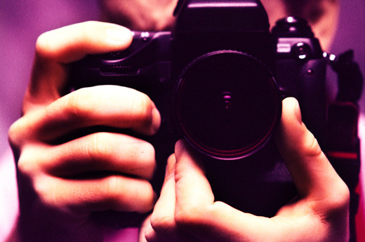 Close-up of human hands holding a camera (toned)