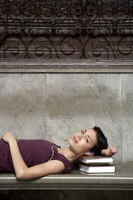Young woman lying on bench, resting head on books, portrait, close-up