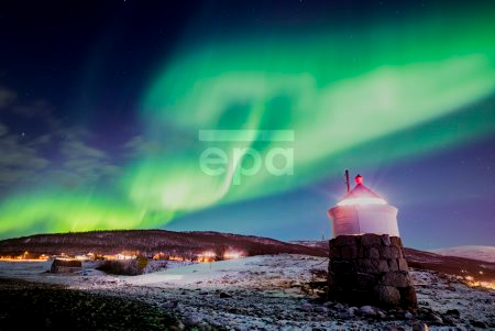 Aurora borealis or northern lights are visible in the sky above a lighthouse to the village of Strand