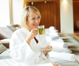 Dame im Bademantel trinkt Tee