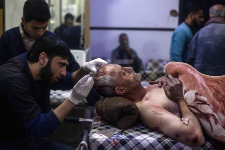 People receive medical treatment after bombing on Douma